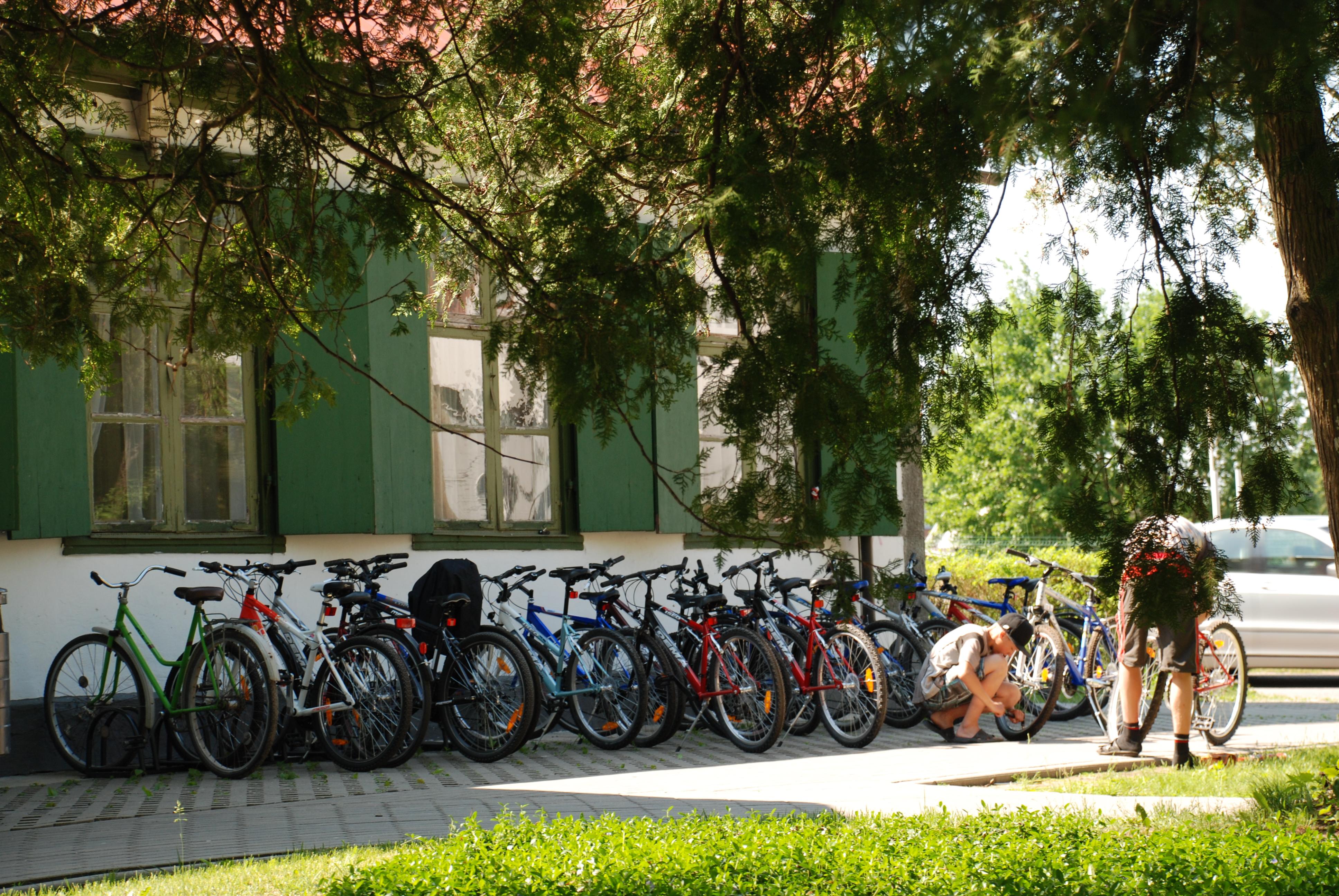 Fotogrāfijā ir attēlots Dienas centrs. Pie tā ir novietotu daudz velosipēdi. Ir vasara. Divi cilvēki pārbauda velosipēdus.