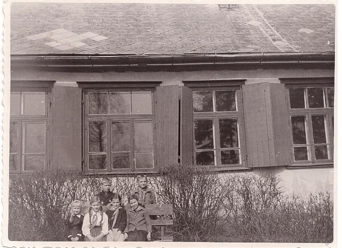 Fotogrāfija attēlo Dienas centru senākos laikos. Bildē ir redzami četri logi, to slēģi ir atvērti. Priekšplānā ir krūmu. Fotogrāfija ir melnbalta.